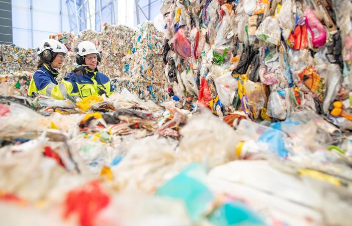 kaksi työntekijää kierrätysmuovin vieressä